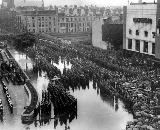 A photograph from North Yorkshire's County Record Office archive showing an open-air service to commemorate Victory in Europe Day in 1945 in Scarborough. Troops are lined up between the railway station, the Odeon Cinema and West Square.