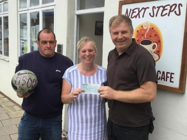 Leisa Burniston, manager at Next Steps receiving a cheque from Malton Veterans players Steve Mason and Mike Todd