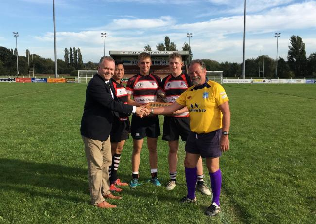 Ben Stone, Malton & Norton RUFC mini and junior chairman, and young players are pictured accepting the East Yorkshire Referees' Society Terry Hardaker Trophy from referee James Harris. Picture: Chris Wilson