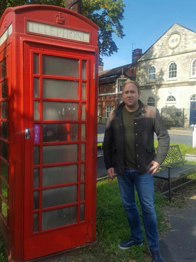 District Cllr Nathan Garbutt Moore next to Rillington's red phone box