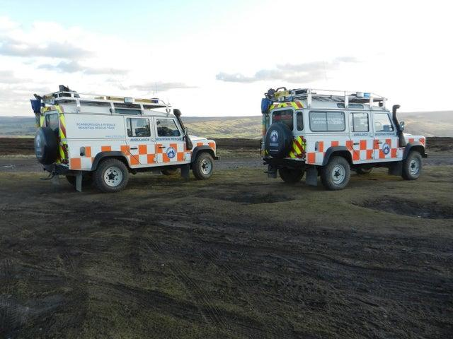Mountain rescue team help man with exhaustion
