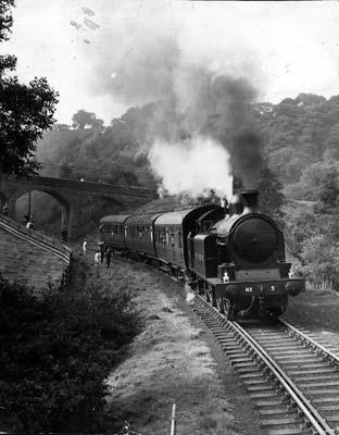 A steam locomotive pulls three carriages on the North Yorkshire Moors railway in the 1970s.