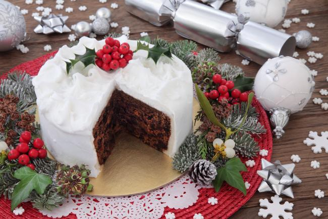 A traditional Christmas cake with holly, bauble decorations and winter greenery over oak background