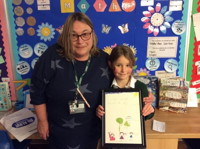 Mandy Carpenter, Leader for Transition/Active Travel, at Malton Primary School, presents Neve Jackson with her prize in the Sustainable Travel Art Competition