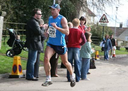 One of the leaders in the Helmsley 10k race running past onlookers outside the church in the town.