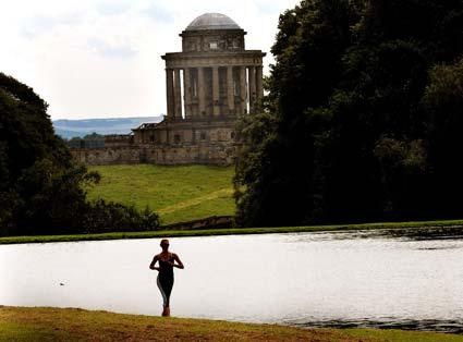 A competitior in the Castle Howard Triathlon is silhouetted against the lake with the mausoleum in the background.