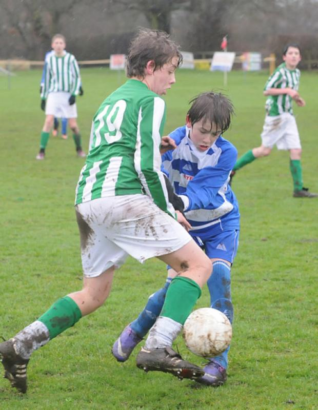 A brave Brooklyn youngster clashes with a Wigginton opponent in the York FA U14s Cup semi-final