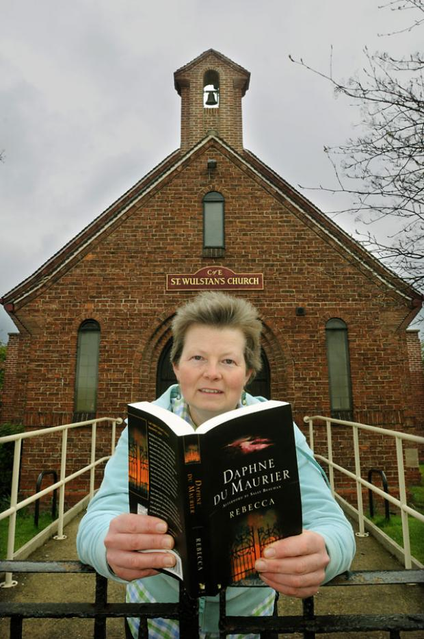 Mary Marchant outside St Wulstan's Church, with a copy of Daphne Du Maurier's Rebecca, which she will be giving away on Monday