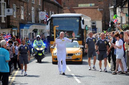 Eugene Perry carries the Olympic Flame on the Torch Relay leg through Thirsk