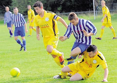 Old Malton St Mary's duo Robbie Baker and Callum Scott put the squeeze on York RI player Ryan Davison (striped shirt)