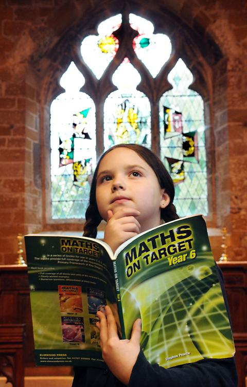 An Alne School pupil puzzles over her maths book in the village church where children are being taught while their own building is renovated