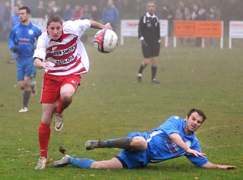 Old Malton St Mary's player Jamie Shepherd slides in but Malton & Norton's Simon Reeves comes away with the ball