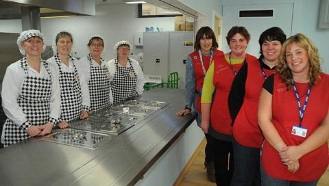 Gazette & Herald: Norton Primary School staff in the newly- opened kitchen and dining hall. Pictured from the left are: Jacqui Milner, Gill Bowman, Anne Mooring, Teresa Teasdale, Helen Pallister, Christine Downing, Clare Towse and Claire Speedie