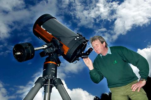 Ranger Mark Barker looks through a telescope in Dalby Forest