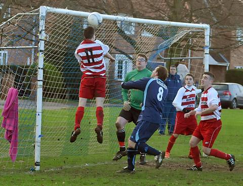 Malton & Norton's Kingsley Daffan (11) clears the ball over his own bar, away from Haxby dangerman Rich Burnett (8)