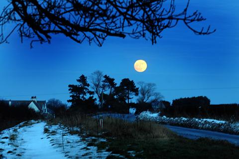 The moon rises in the cloudless sky over a wintery setting near Ganton