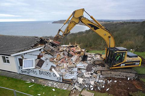 The cliff top house,  bought by artist Kane Cunningham, after the demolition  contractors moved in with their bulldozers. Pictures: Tony Bartholemew