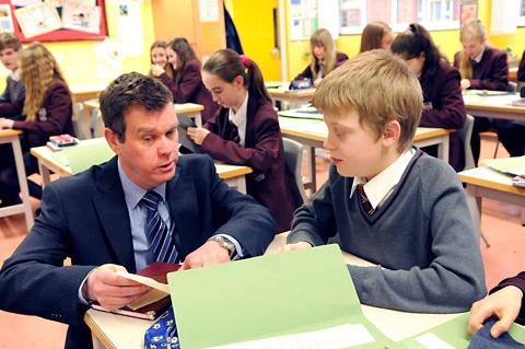 Norton College headteacher Phil Loftus talks to pupil Lewis Stead, 12, during a Year 8 textiles lesson