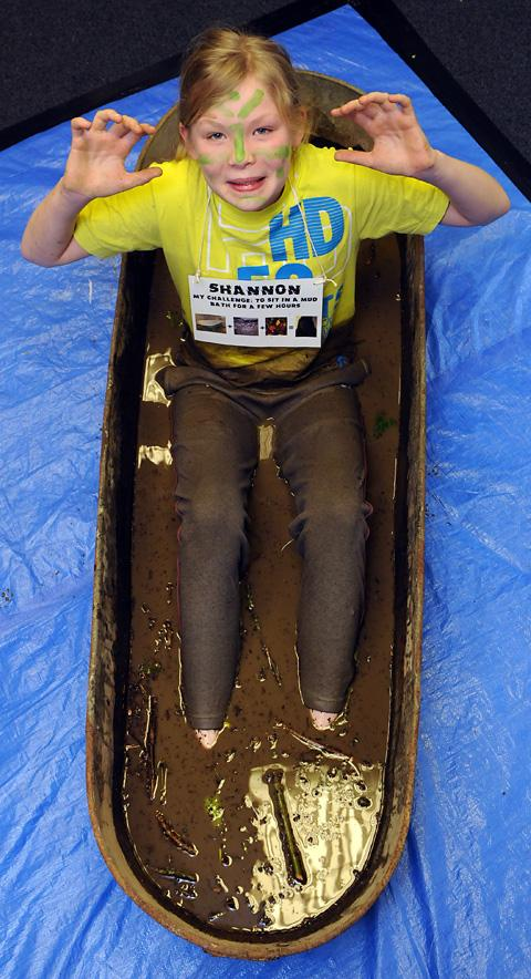 Shannon, 11, sits in a mud bath during ghe X:Talk Raise It Weekend