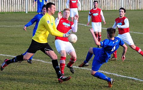 Thackley goalkeeper Tom Carlisle saves under pressure from Pickering Town's Lewis Taylor