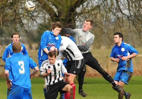 Old Malton 'keeper Robbie Thackray punches clear against Dunnington