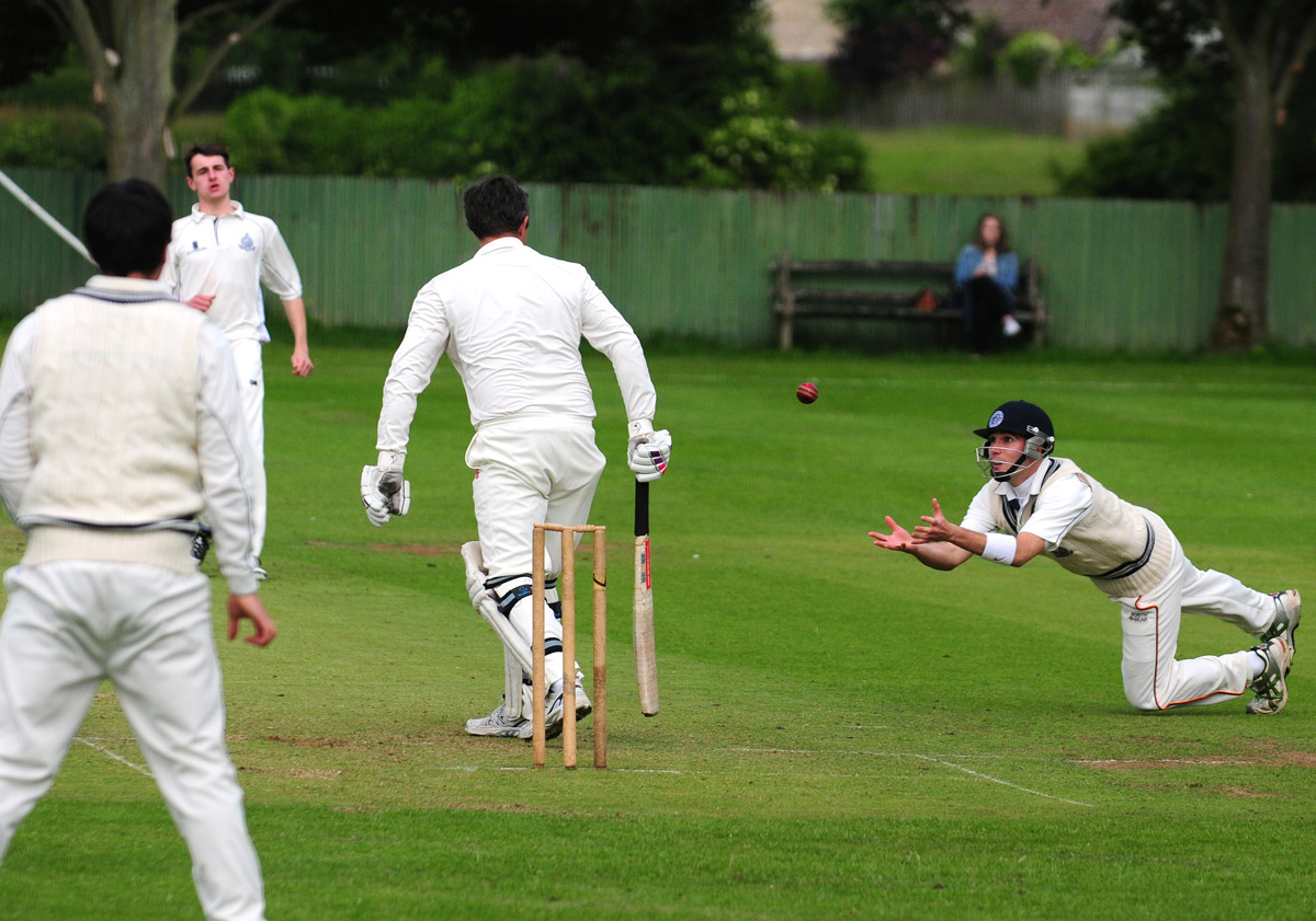 Scarborough II's short leg fielder Josh Mainprize dives forward to make a catch, but prolific Duncombe Park opener Brian Leckenby survived as the ball came off his pad