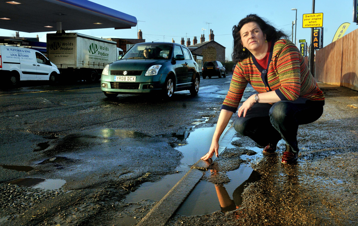Di Keal points to the potholes in Church Street, Norton