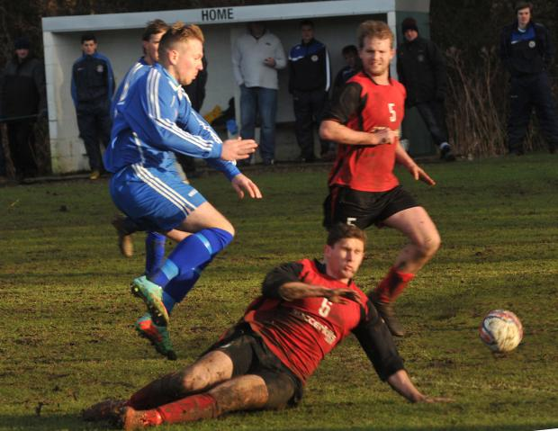 Gazette & Herald: Old Malton St Mary's  striker Marcus Godsell  hurdles a tackle from a Terrington Glory  player in  his side's  1-0 home win in the York Minster Engineering Football League  premier  division