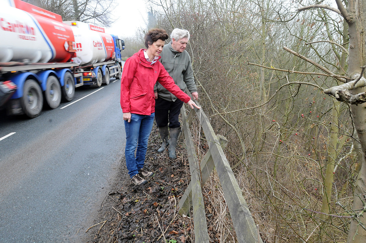 Kate Megginson and Lord Middleton look over the edge into the steep drop from the road on Grimston Hill which they feel is dangerous