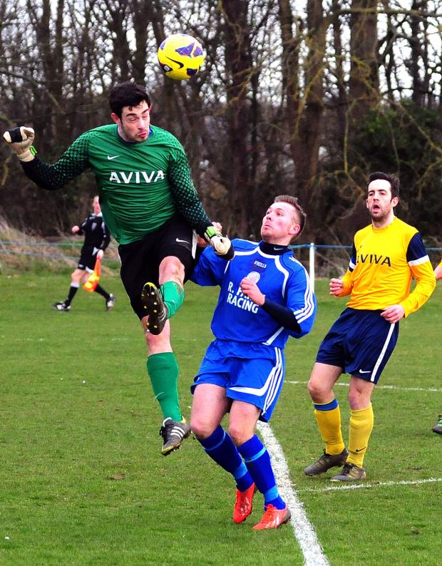 Gazette & Herald: Aviva keeper Dan Cowton heads clear on the edge of the box from Old Malton St Mary's Marcus Godsell.