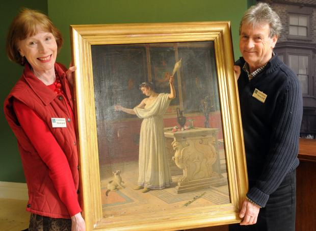 Volunteers Christine and Malcolm Barnard with a painting donated to Malton Museum by Dr James Kirk and rediscovered and put on display. Picture : Garry Atkinson