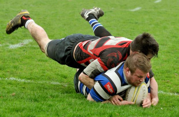 Malton & Norton flanker Rob Mewburn hangs onto a Driffield player but fails to stop his scoring a try