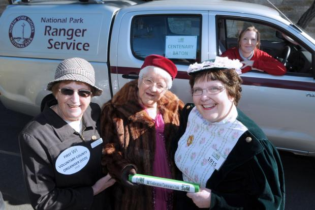 National Park Ranger Naomi Green in the driving seat  at Helmsley with (foreground, from left) Pat Shotton, Freda Shaw and Janice Whiteford, of the North Yoshire East Federation of WIs, with the centenary baton.