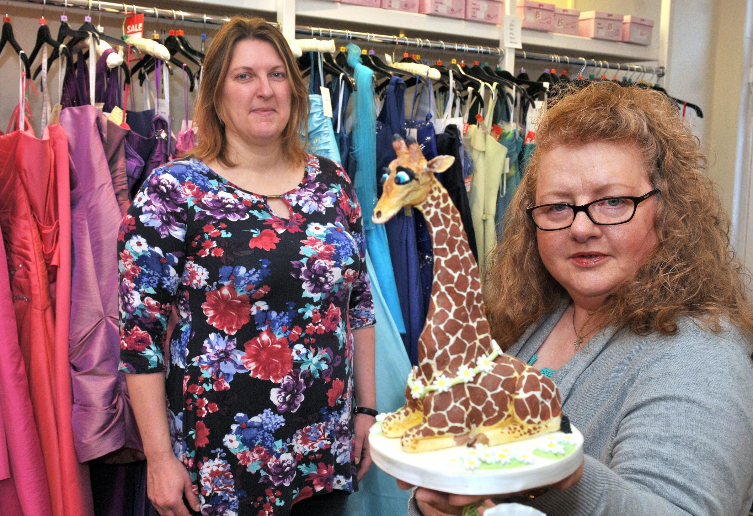 Josie Abbey (right) holds a decorative giraffe cake at Perfect Day bridal salon Malton watched by Mell JEFFERY (correct).Josie wants to open a Malton branch of the British Sugar Craft Guild.