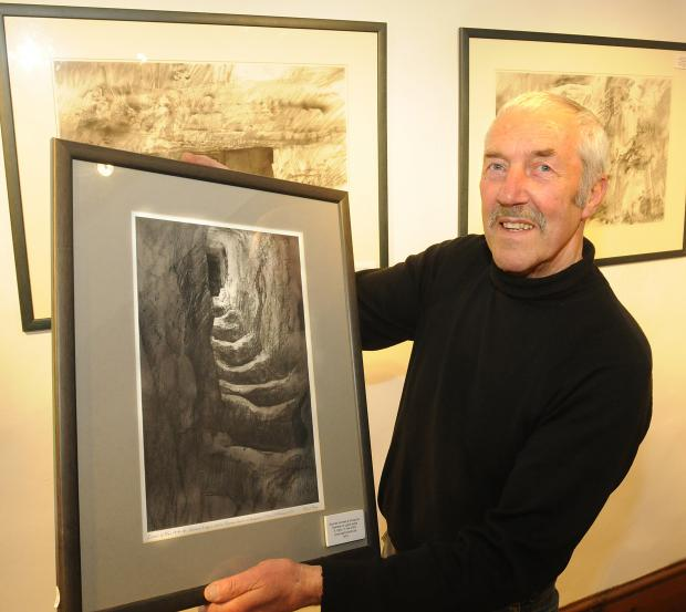 Robert Perry with one of his pictures showing shattered infantry shelters at Verdun on the World War One battlefields which is one of the drawings and paintings done on site that are now an exhibition at Nunnington Hall