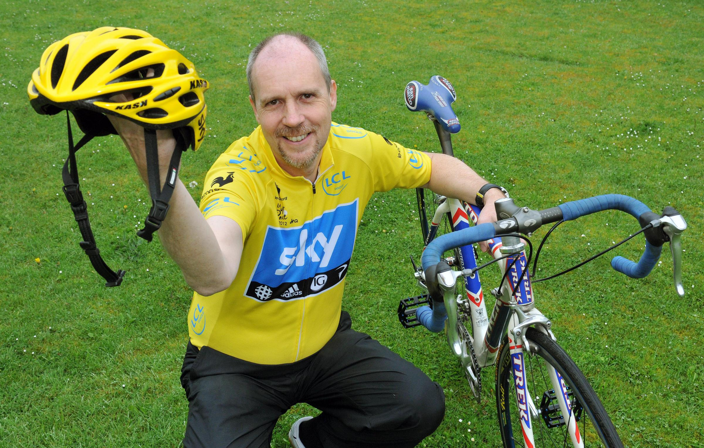 Author Andy Seed holds the cycling helmet worn by last year's winner of the Tour de France Chris Froome