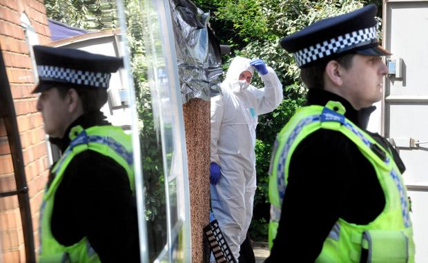A forensics officer works in the back garden of the house in Burnholme Grove as a PCSO guards the scene