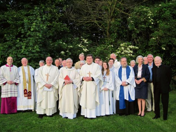 Father Tim Bywater (centre) surrounded by clergy and others from various churches