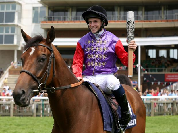Gazette & Herald: Ryan Moore with the Queen's Baton as he rides D'arcy Indiana at Newmarket