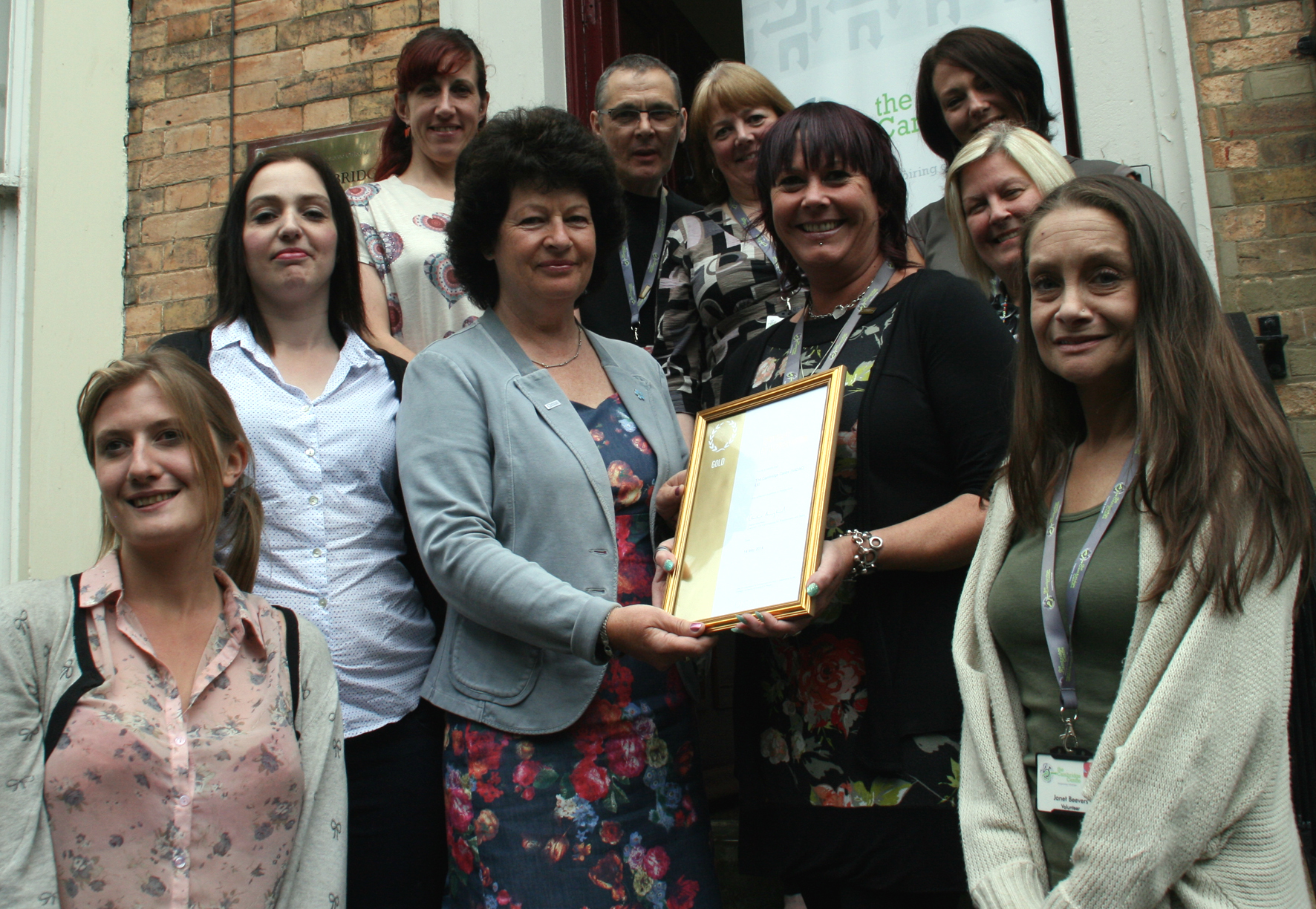 Anne Stockdale, Investors in People Specialist for the region, left, and Cambridge Centre Chief Executive Nikki Orrell, right, with the Investors in People Gold certificate, surrounded by staff from the centre.