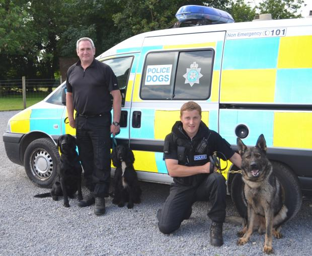 PC Vince Gillon, left,  with trainee police dogs Jacob and Atom and PC Martin Gayles with Thor