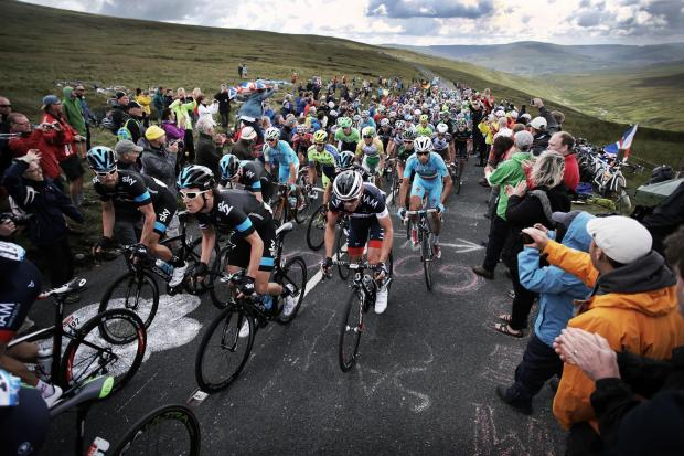 Spectators line the roads of the Dales as reigning champion Chris Froome and his Sky team-mates go over the top of Buttertubs Pass during the Tour de France's incredible visit to Yorkshire
