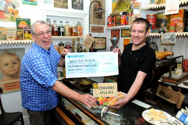 Bruce Pickup, left, of the Beck Isle Museum, receives the cheque from Jeremy Smith, of Costcutters in Pickering