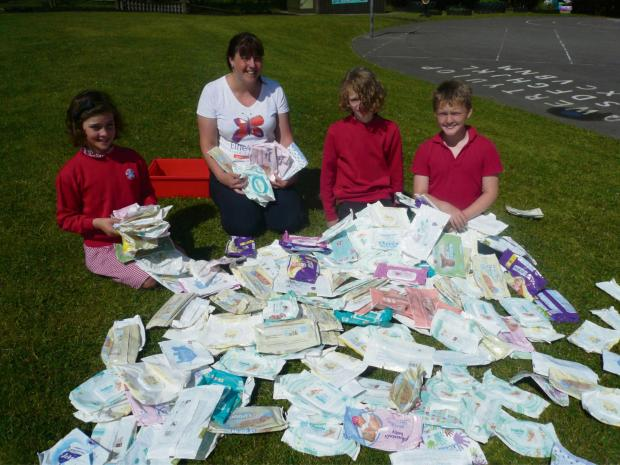 West Heslerton Primary School pupils Alicia Davison, Finley May and Nathan Dukes, with Heather Othick, from Ellie's Fund, and some of the baby wipe packets they have collected