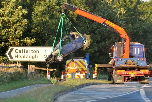 The blue Renault Clio is hoisted away by a crane after the crash on the A64 in which one man died