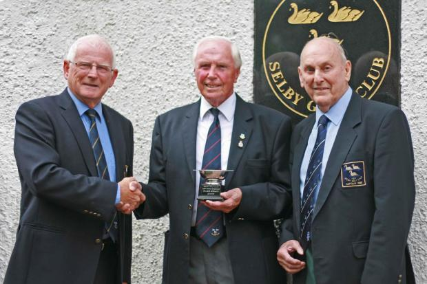 Colin Railton, centre, receives the trophy from club captain John Bowness, left, watched by Jack England, in whose honour the trophy is named