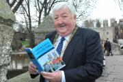 The Lord Mayor of York Councillor Ian Gillies with a copy of A Walking Guide To York's City Walls by Simon Mattam