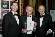 Paul Bellinger, centre, collects his award from Gyles Brandreth, right, at the Farm Business Food and Farming Industry Awards