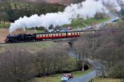 A steam train powers over a railway bridge at Moorgates, near Goathland
