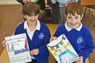 Helmsley Primary School pupils Anja Dowson and Oliver Thompson with their winning posters being presented with their book prizes by Ken and June Claridge from Claridge's book shop